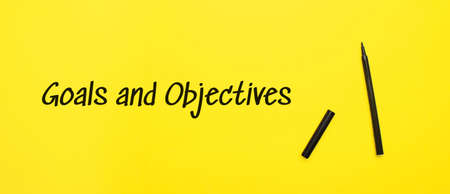Goals and Objectives sign with black marker on a yellow background. With copy space ready for your text.