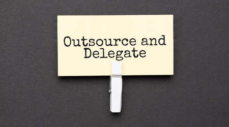 outsource and delegate text on paper with wihte clip. On black background Banco de Imagens