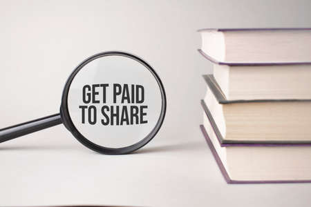 The inscription Get Paid To Share is written and the books. Content lettering is essential for business content and marketing.