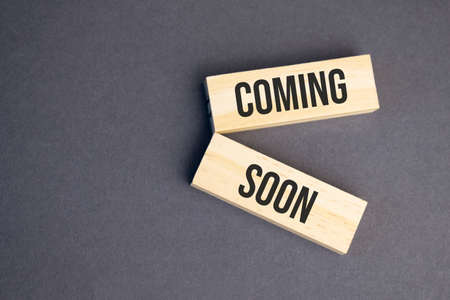 Coming Soon words on wooden blocks on yellow background. Business ethics concept. Banco de Imagens