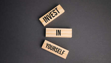 Invest in Yourself words on wooden blocks on yellow background. Business ethics concept.