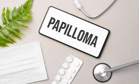 Papilloma word on smartphone, stethoscope and green plant