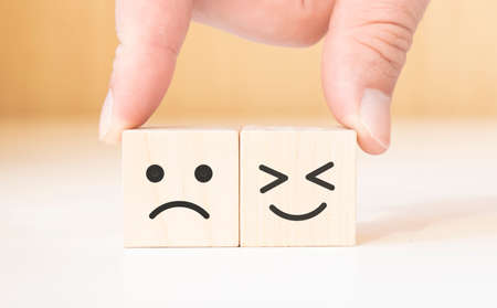 Hand holding smile and sad face symbol on wooden cube blocks. Emotion, Service rating, ranking, customer review, satisfaction and feedback concept