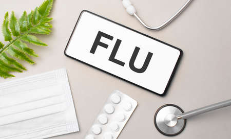 flu word on smartphone, stethoscope and green plant
