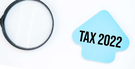 magnifying glass with blue arrow paper sheet with text tax 2022