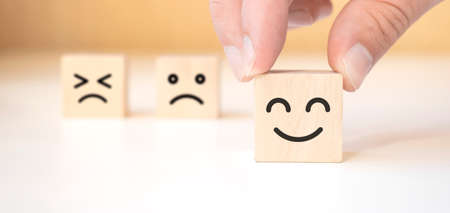 A man holds a wooden cube with a picture of a positive face on the background of negative emotions. Close up.