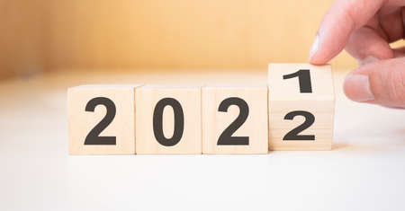 Businessman hand holding wooden cube with flip over block 2021 to 2022 Plans word on table background.