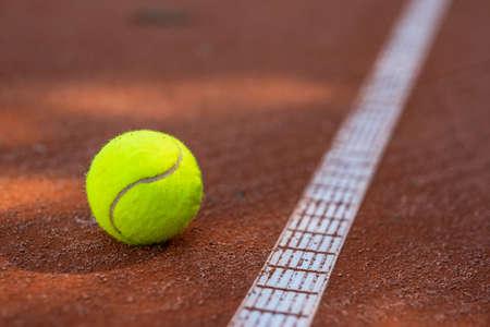 Closeup of one tennis ball close to a white line on a slug court