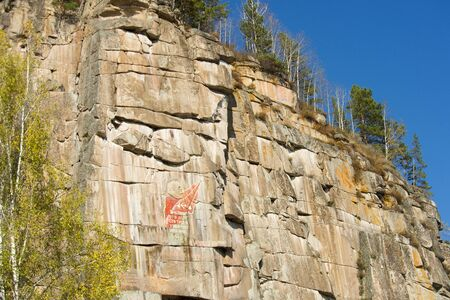 vandalism: Lenins portrait soiled by paint and inscriptions on the mountain at Teletskoye Lake Stock Photo