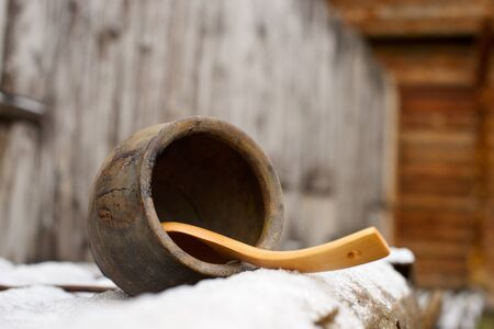 Clay pot, wooden spoon isolated on a wooden stakes background, Russia