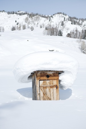 an old rustic weathered wooden outhouse in the snow