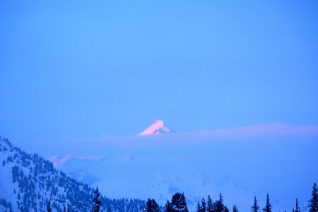 highest mountain peak at dawn, bathed in pink colors