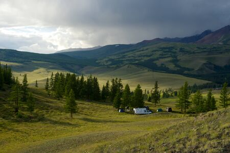 Beautiful sunny valley between the mountains with lush clouds in the Altai Republic
