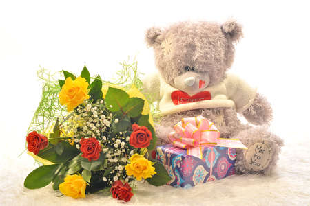 Teddy bear with a bouquet of flowers and a gift photo