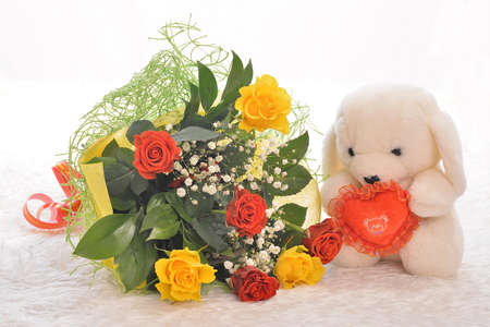 Teddy bear with a bouquet of flowers and heart photo