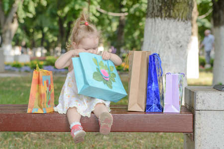 baby girl on a bench with shopping gifts