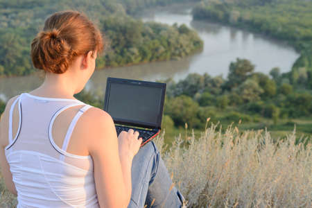 telecommunicating: Girl with a computer on nature Stock Photo