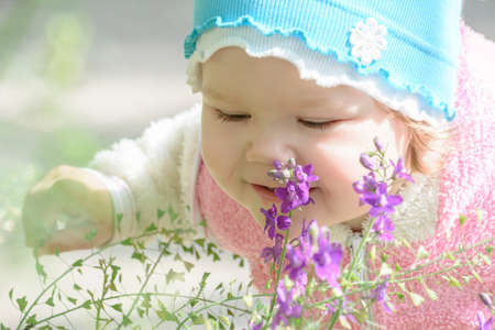 little girl leaned over to him to smell a flower photo