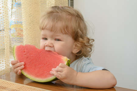child holding a slice of watermelon and bites her photo