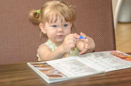 child in a restaurant looking menus and make a reservation photo