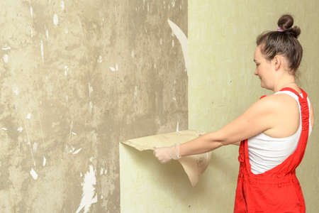 scraping: woman breaks the old wallpaper from the walls