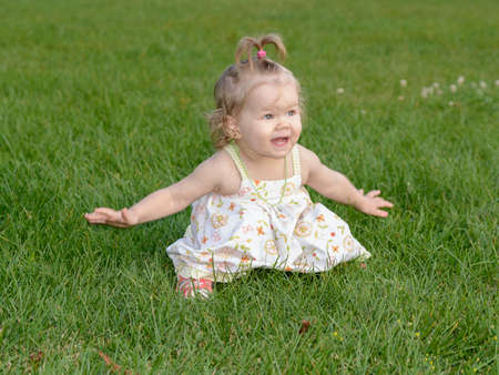 baby 4 5 years: little girl sitting on the grass Stock Photo