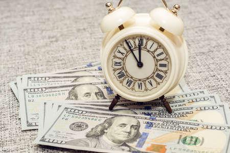 monies: alarm clock on the a hundred dollar bill