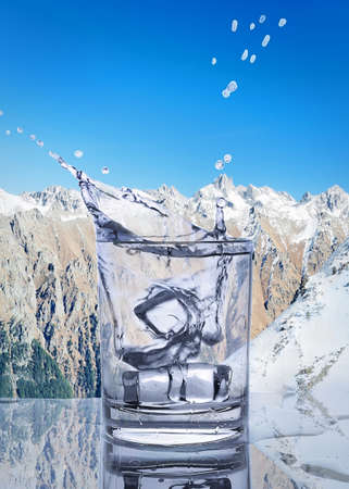 falling ice cubes in a glass of water Stock Photo