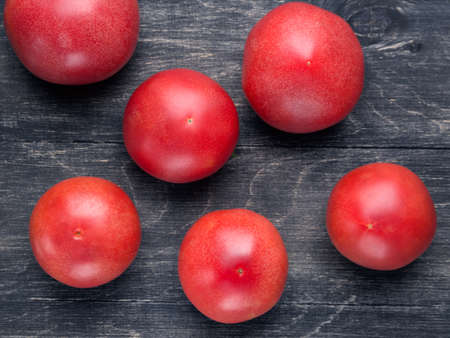 four objects: few ripe tomatoes lying on a wooden surface Stock Photo