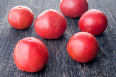 několik zralých rajčat ležících na dřevěném povrchu