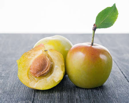 alycha: plum lying on a wooden surface