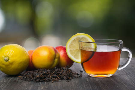 cup of tea with a slice of lemon and fruit with tea leaves Stock Photo