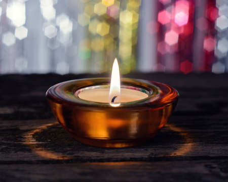 a lighted candle in a candlestick Stock Photo