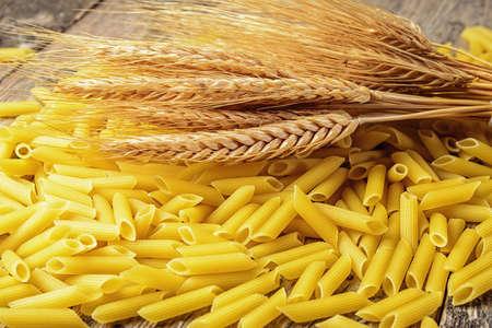 Macaroni products and ears of ripe wheat Фото со стока