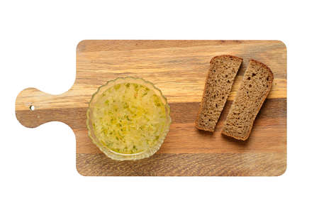 a plate of soup stands on a cutting Board and next to it are two pieces of gray bread Banco de Imagens
