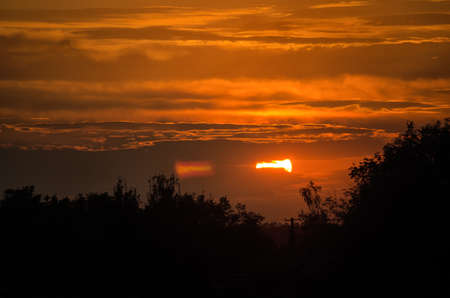 the sun shines from behind the clouds at sunset