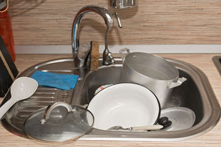 dirty dishes lying in a metal sink