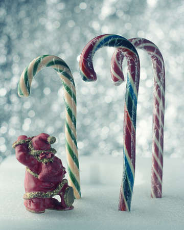 Christmas candies of different colors on a beautiful background and a figure of Santa Claus
