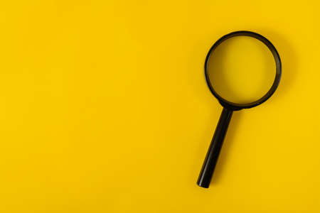 magnifying glass on a yellow sheet Archivio Fotografico