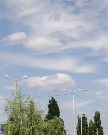 sky with clouds over trees and pillars with lanterns Archivio Fotografico
