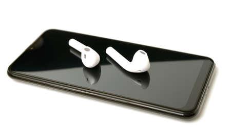 white wireless headphones lie on the smartphone