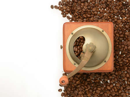 mechanical coffee grinder with ground coffee next to a lot of beans