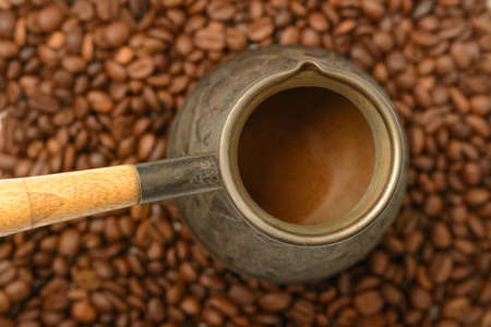 Turk with ready-made coffee on coffee beans