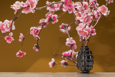 Grenade bomb on a table with sakura twigs on dark orange background