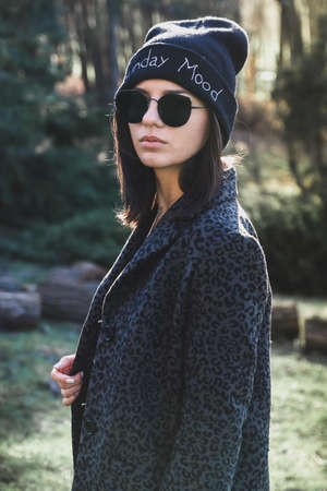 Street style portrait of a girl with black sunglasses and black hat on into the woods looking away Stock Photo