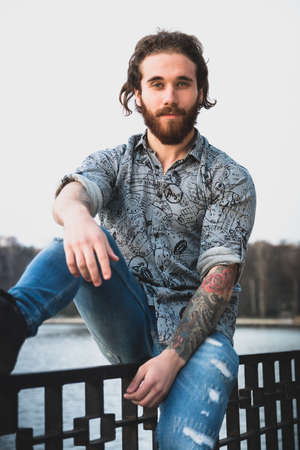 Portrait of young bearded handsome man with tattooed body looking sexually at camera near a lake