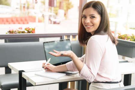 Joven estudiante en café trabajando en equipo portátil se volvió y preguntó.