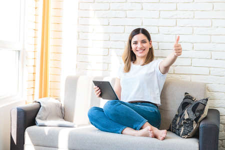 Technology, internet and people concept - happy attractive woman with tablet computer showing thumbs up at home