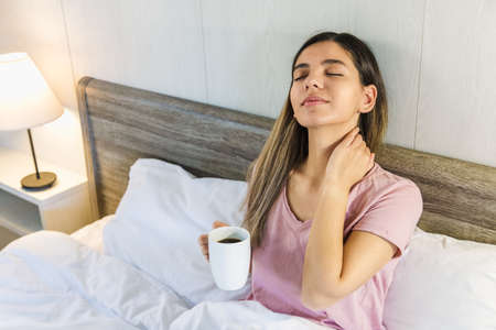 woman sitting on bed with eyes closed holding a cup of coffee or tea