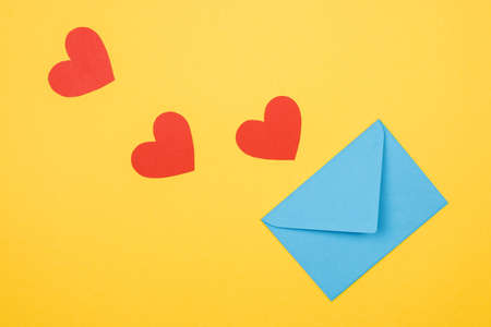 three decorative red hearts and envelope on yellow background